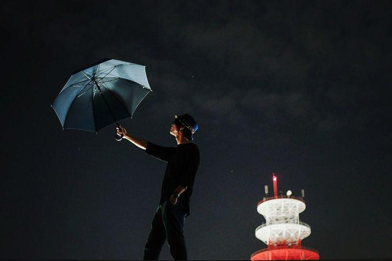 Man holding illuminated lighting equipment at night