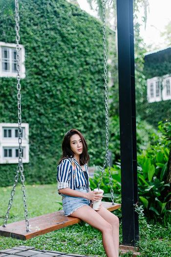 Portrait of woman sitting on swing