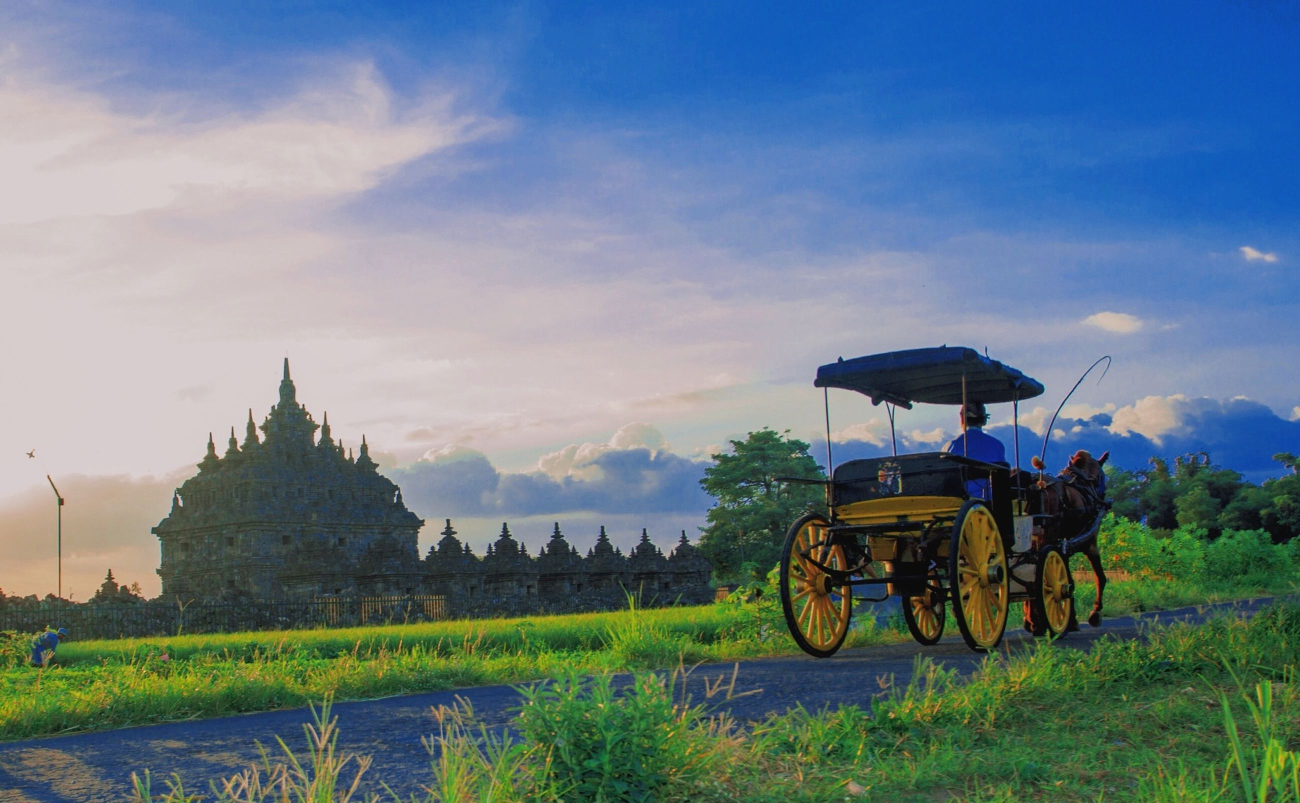 transportation, sky, mode of transport, land vehicle, bicycle, grass, cloud - sky, landscape, travel, architecture, tranquility, field, cloud, building exterior, built structure, nature, scenics, tranquil scene, stationary, plant