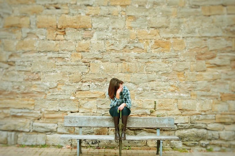 Full Length Of Woman Sitting Against Brick Wall