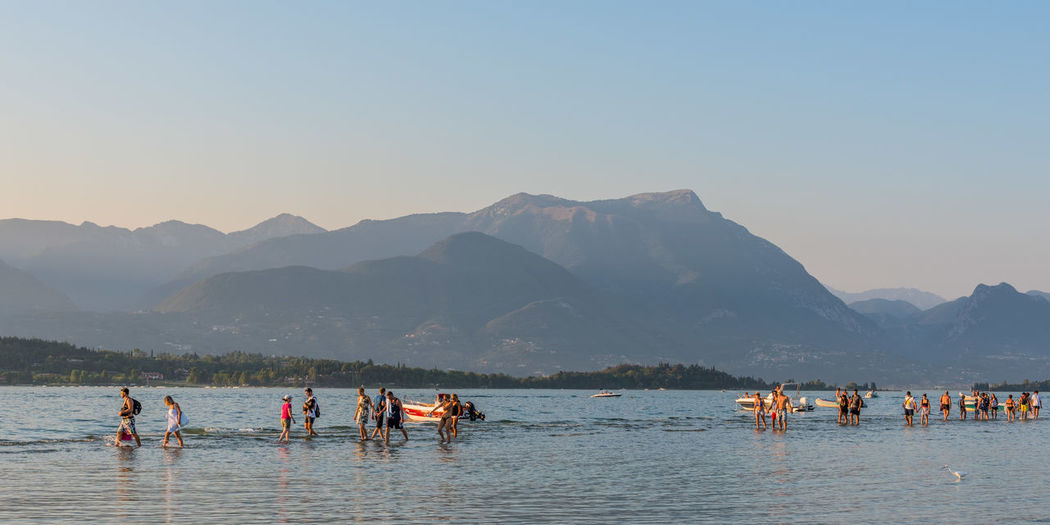 People in lake garda against mountains at san giorgio maggiore
