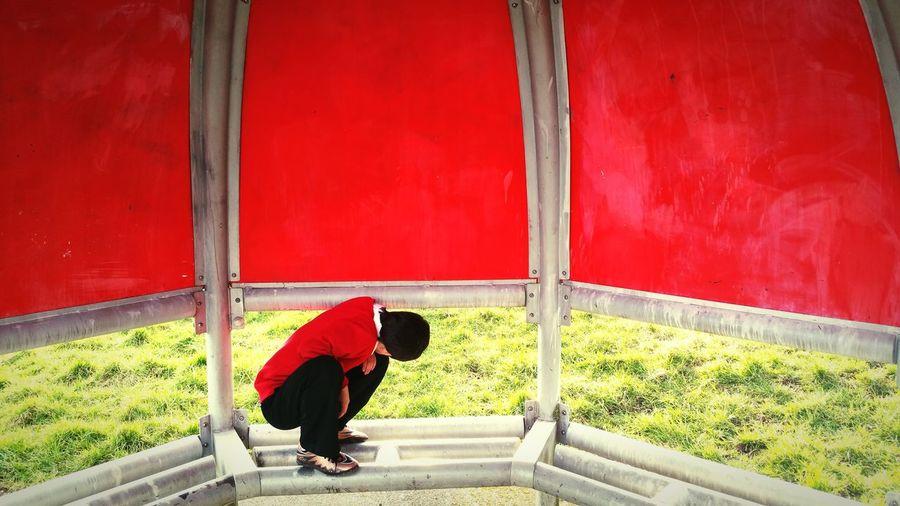 Full length of boy crouching at red gazebo at park
