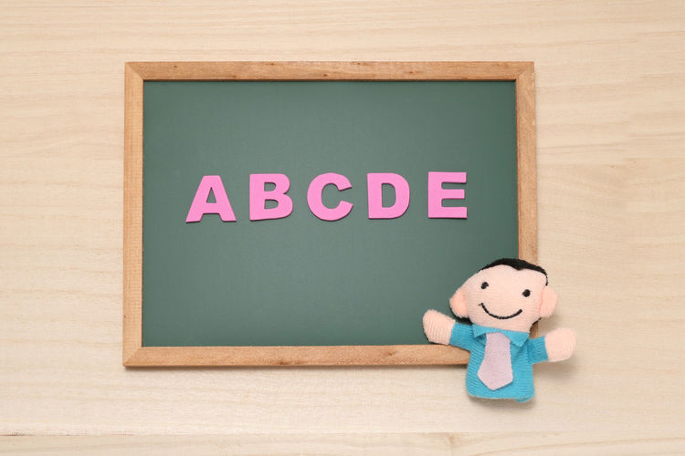 High angle view of blackboard with alphabets and toys on table