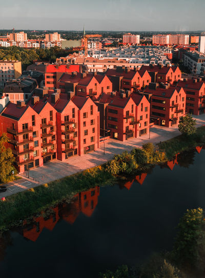 High angle view of river by houses against sky