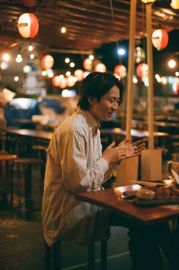 Side view of woman at restaurant table at night