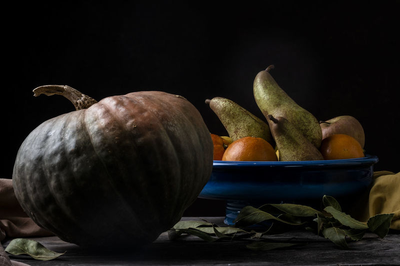 Close-up of fruits on table against black background