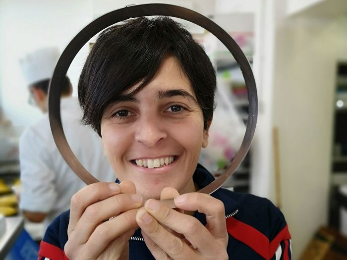 Portrait of smiling woman holding circular picture frame
