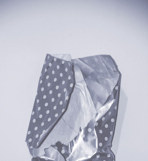 Close-up of paper wrapped over white background