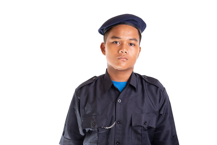 Young Asian man in police uniform isolated on white background. White Background Studio Shot Cut Out One Person Clothing Looking At Camera Standing Young Adult Cap Portrait Men Police Officer Security Face Smile Service Front View Young Men Indoors  Confidence  Copy Space Hat