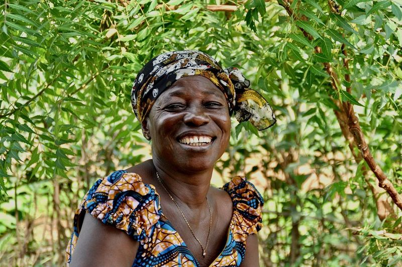 Smiling mature woman outdoors against tree