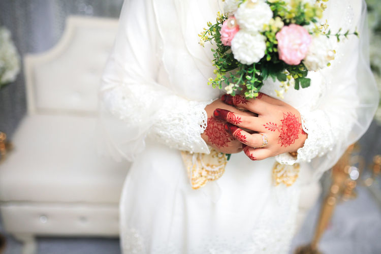 Midsection of bride holding bouquet during wedding ceremony