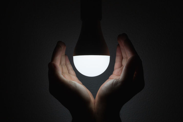 Close-up of hand holding illuminated lamp against black background