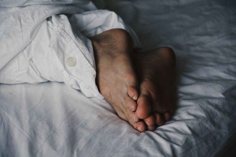 Low section of man sleeping on bed
