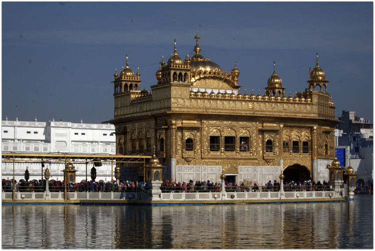 Golden temple by pond against sky