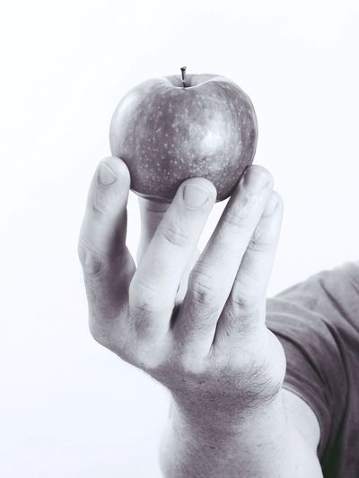 Close-up of man holding apple against white background
