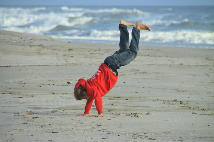 Teenage boy doing handstand at beach
