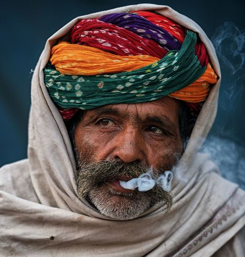 Close-up of man looking away while emitting smoke