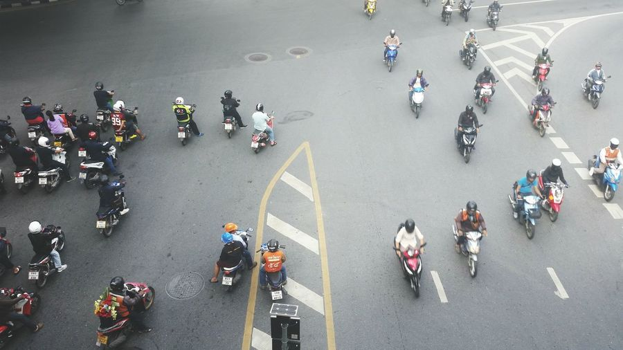 High angle view of people with motorcycles on road in city