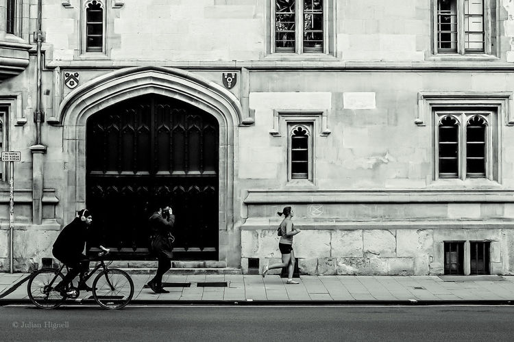 Man riding bicycle on street against building