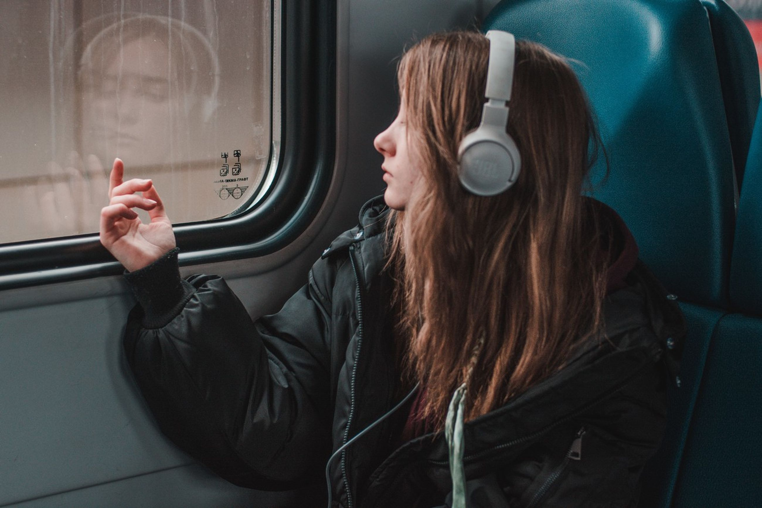 one person, real people, music, headphones, lifestyles, indoors, leisure activity, listening, vehicle interior, casual clothing, mode of transportation, long hair, women, transportation, young adult, hairstyle, public transportation, adult