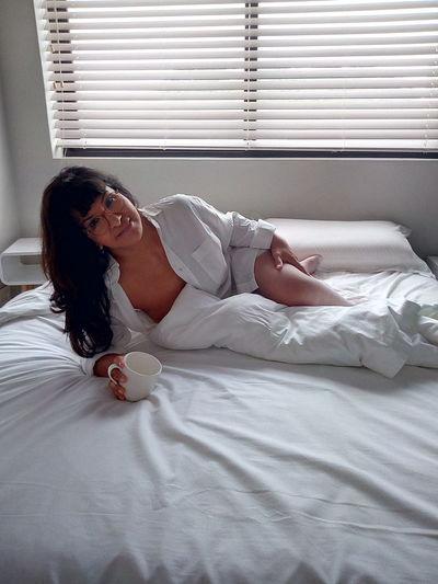 Portrait of seductive woman holding mug lying on bed