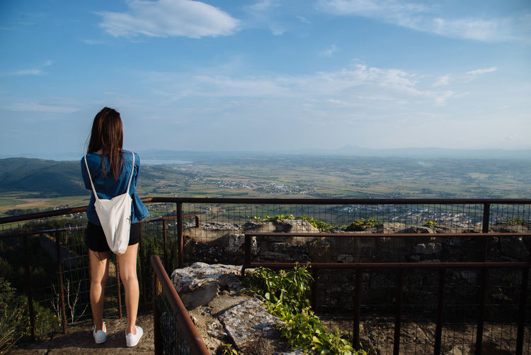 Rear View Of Woman Standing At Observation Point Against Landscape