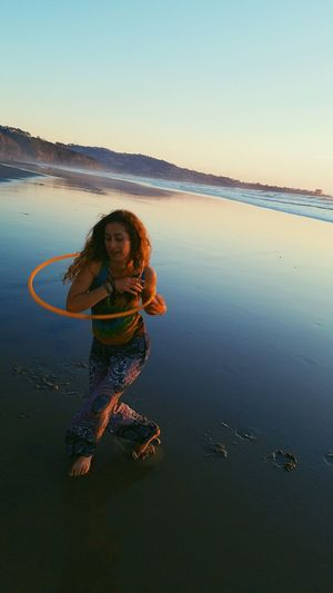Young woman spinning hoop at beach
