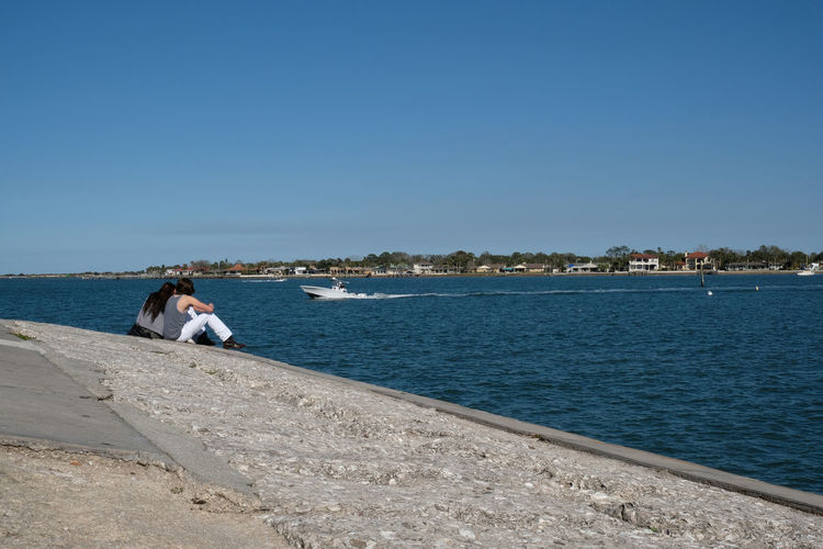 Young couple talk as they sit on a rock wall and look at the beach houses across the Matanzas River as a speed boat passes. St Augustine, Florida, USA. Man in white trousers and cowboy boots. Castillo De San Marcos Clear Sky Couple Couple - Relationship Couples Couples In Love Couplesphotography Couples❤❤❤ Day Nature Outdoors Sky St Augustine St Augustine Florida St Augustine, FL