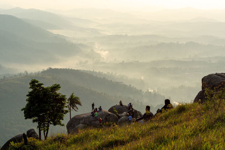 People sitting on landscape against mountains