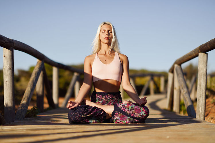 Full length of young woman meditating while sitting on boardwalk against sky