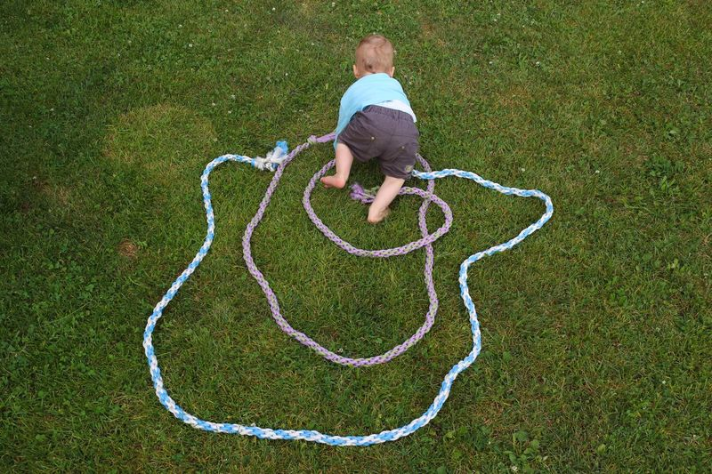 Full length of boy playing with rope on field