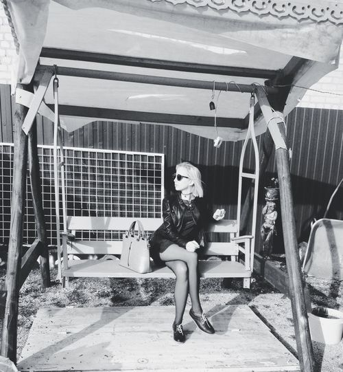 Young woman wearing sunglasses sitting on swing