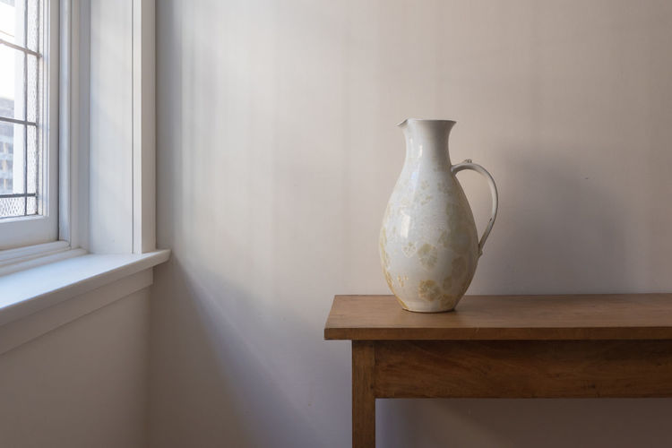 Jug on table next to window Indoors  Table No People Container Wood - Material Window Day Home Interior Seat Vase Still Life Domestic Room Ceramics White Color Pitcher - Jug Nature Absence Wall - Building Feature Close-up