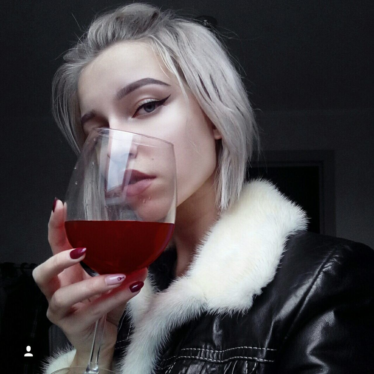 wineglass, young adult, drinking, real people, one person, drink, front view, young women, wine, lifestyles, red wine, leisure activity, holding, looking at camera, indoors, drinking glass, close-up, portrait, beautiful woman, alcohol, black background, blond hair, warm clothing, day, people