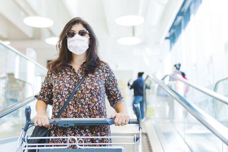 Portrait woman wearing mask standing in supermarket