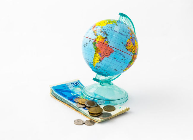 A money box made in the form of a globe, the planet Earth with a money slot at the top stands on a stack of Israeli banknotes of different value with several coins, isolated on a white background. Business Currency Earning Earth Isolated Art Bank Banknote Buy Cash Coin Coins Design Exchange Finance Globe Israel Money Pay Planet Shekel Stock Studio Shot Wealth White Background