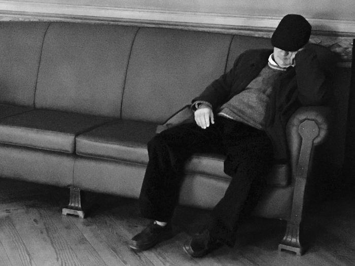 Rear view of man sitting on floor