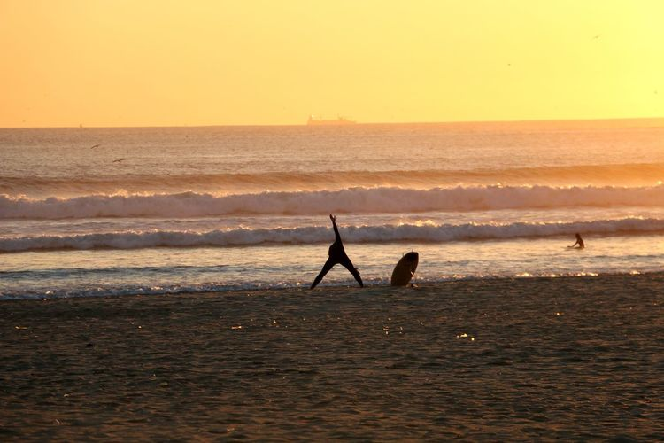 Person Exercising At Beach Against Sky During Sunset