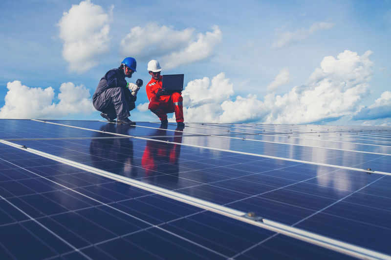 Low angle view of male technicians working on solar panels against sky