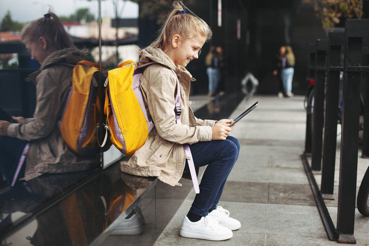 Girl using tablet in city