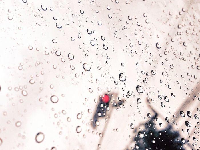 Stoplight Seen Through Wet Car Window During Rainy Season