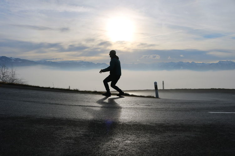 Full length of silhouette man skateboarding on road against sky