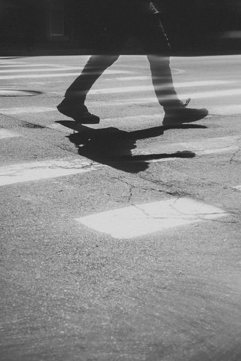 Low section of person skateboarding on street