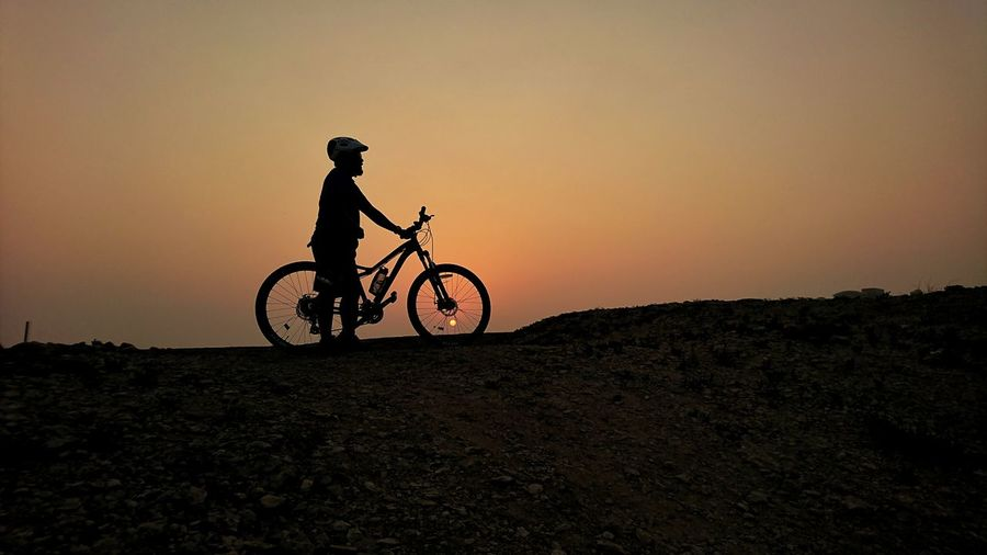 Silhouette man with bicycle on field against sky during sunset