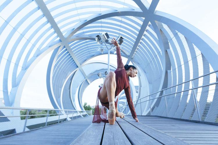 Full length of ballerina dancing on footpath