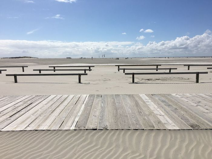 Empty Benches With Boardwalk On Sand At Beach Against Sky