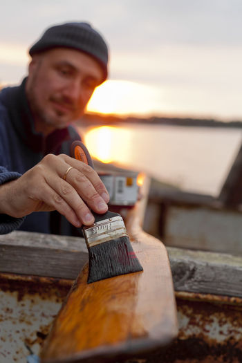Portrait of young man holding wood against sky during sunset