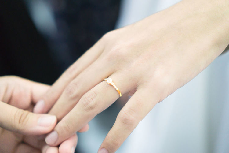 Cropped groom holding groom hand