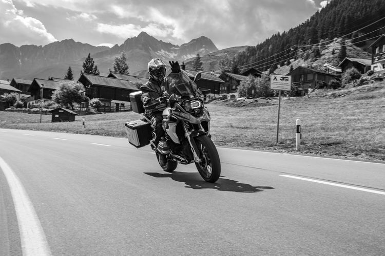 Man riding motorcycle on road against mountains