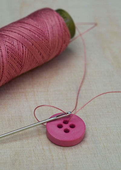 High angle view of pink thread with button and needle on table
